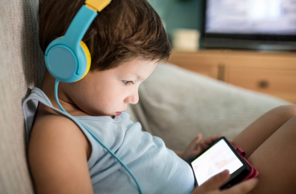A child sitting with headphones on looking at a screen impacting their eye health