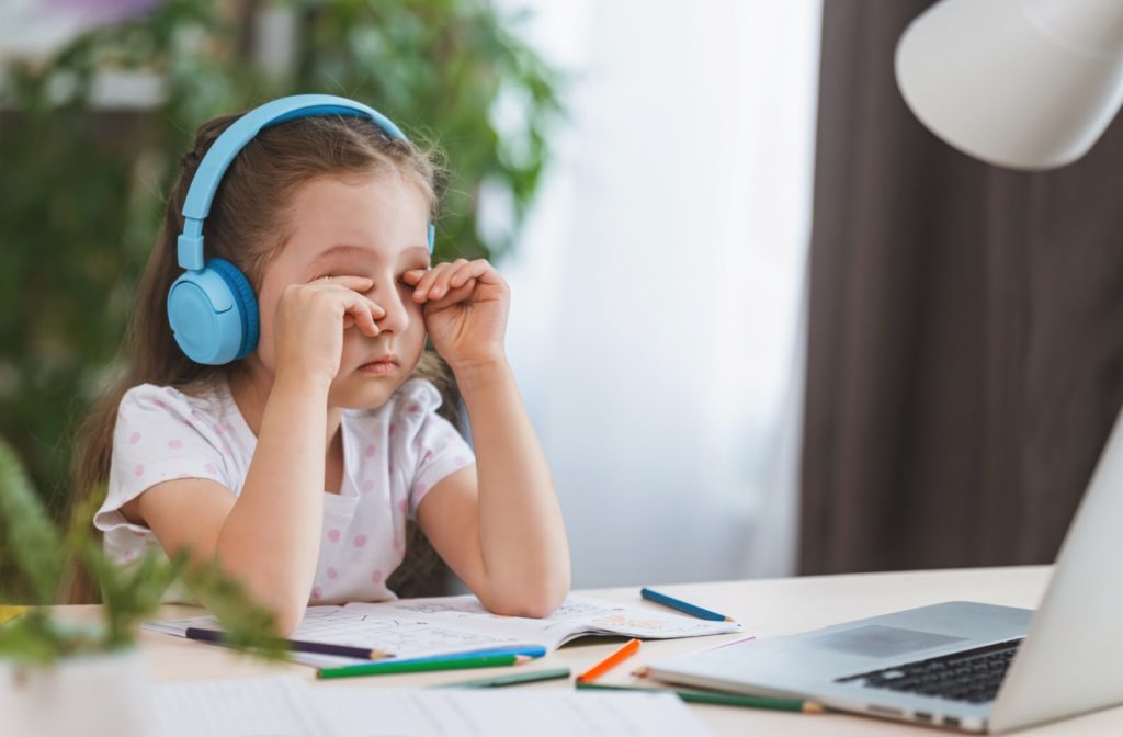 A little girl rubbing her sore, tired eyes from looking at a laptop screen for too long