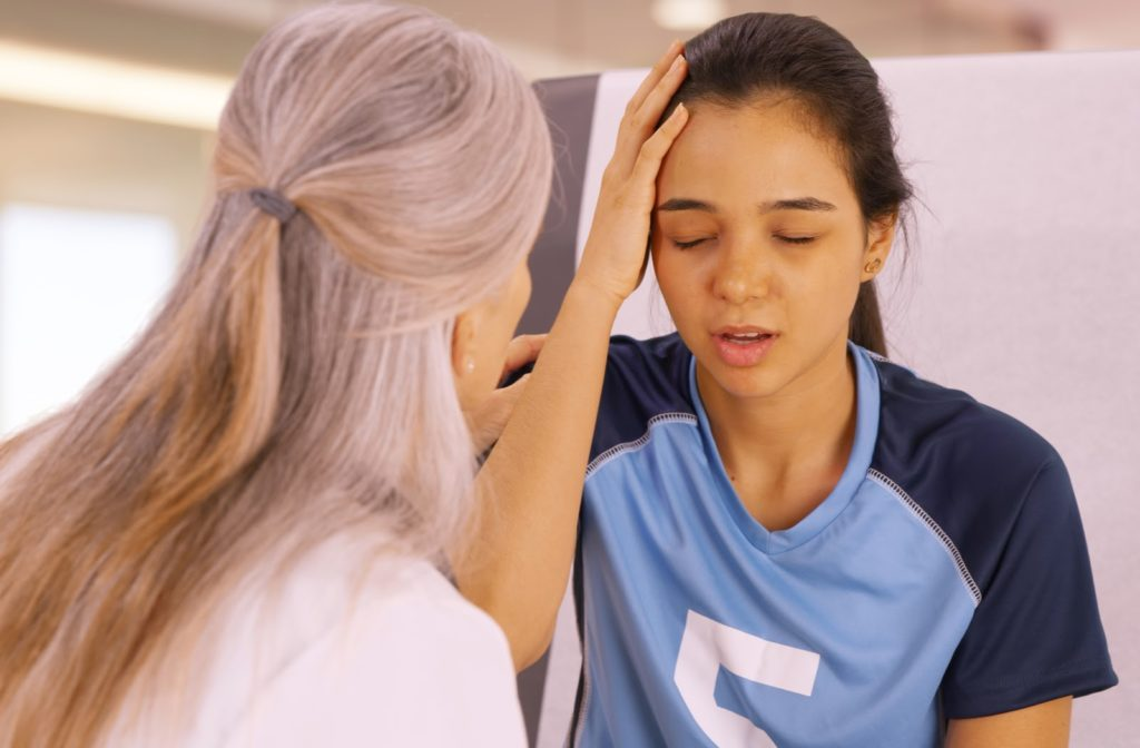 A young girl who is concussed from playing soccer seeking help at a doctors office